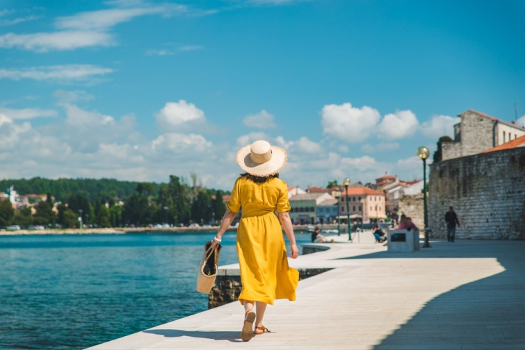 woman walking by sea quay in summer day in yellow sundress. summer vacation
